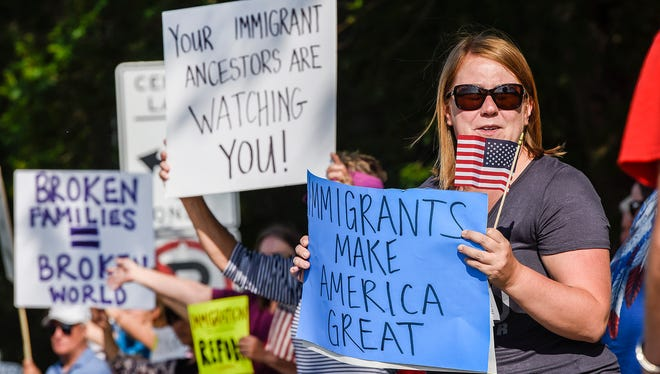 Kayli Schaaf, Coon Rapids, holds a sign with demonstrators from Indivisible MN03 and Indivisible North Metro while protesting the U.S. Immigration and Customs Enforcement (ICE) detaining of immigrants Wednesday, June 27, outside the Sherburne County Government Center in Elk River. The Sherburne County Jail is one of three facilities where Immigration Customs Enforcement (ICE) are detaining immigrants in Minnesota.