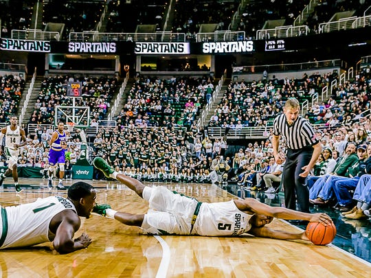 Cassius Winston ,right , of MSU dives to stop a loose ball from going out of bounds after it got away from teammate Josh Langford ,left, late in the 2nd half of their game Saturday December 10, 2016 in East Lansing.  KEVIN W. FOWLER PHOTO