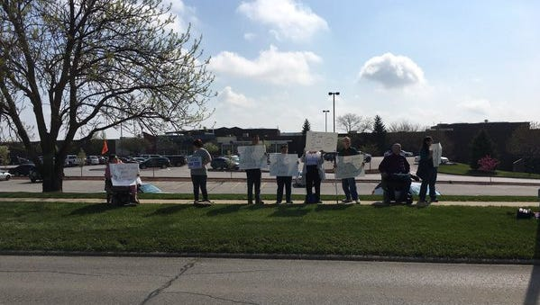 A crowd gathered on sidewalks by Valley West Mall on Saturday to protest the mall's decision to move a DART bus stop off of its property.