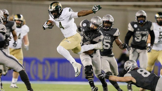 CSU receiver Michael Gallup is tripped up by Air Force defenders Grant Ross (44) and Weston Steelhammer (8) during Saturday night's game at Falcon Stadium. CSU needs to win one of its final two regular-season games to qualify for a bowl game for the fourth year in a row.