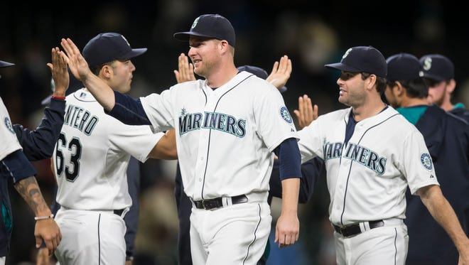 Seattle Mariners' Mark Trumbo, center, and teammates, including Jesus Montero, left, and Seth Smith, celebrate following a baseball game against the Texas Rangers, Wednesday, Sept. 9, 2015, in Seattle. The Mariners won 6-0 .