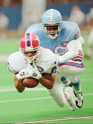 Bills wide receiver Andre Reed (83) catches a pass for a gain of 10 yards as Houston Oilers cornerback Darryll Lewis (29) moves in to tackle him during  a game on Sept. 18, 1994, in Houston.