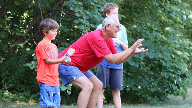 Cooper Albers, left, and Ron Janke, right, enjoy a water balloon toss at Lakeside on Saturday.
