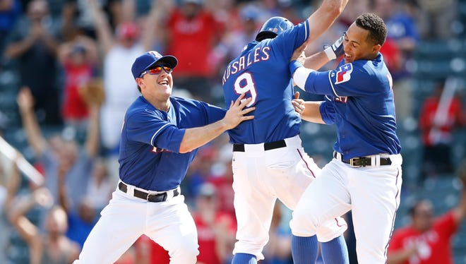 Texas Rangers third baseman Adam Rosales celebrates hitting a walk-off single during the ninth inning to beat the Los Angeles Angels with teammates Daniel Robertson (left) and Leonys Martin (right) at Globe Life Park in Arlington.