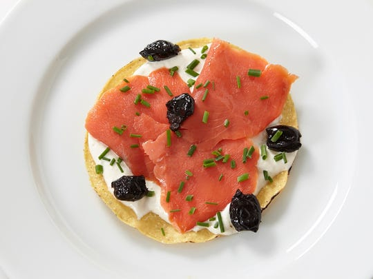 """An easy, quick and attractive appetizer from Jacques Pépin's new book, """"Heart & Soul in the Kitchen,"""" includes salmon tostadas, which features a mayonnaise, yogurt and horseradish mixture, spread on crisp tostadas and topped with pieces of smoked salmon sprinkled with chives."""