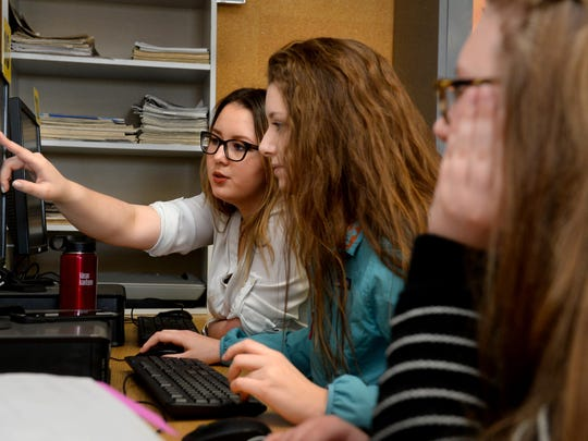 Terryn Premo, left, the senior editor-in-chief of the CMR High School yearbook, Russellog, works with Josey Quinn during Wednesday morning's class.