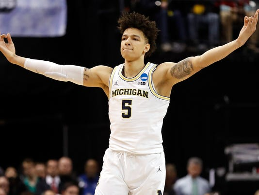 FILE - In this March 17, 2017, file photo, Michigan's D.J. Wilson celebrates after hitting a 3-point basket during the team's first-round game against Oklahoma State in the men's NCAA college basketball tournament in Indianapolis. The Milwaukee Bucks selected Wilson in the NBA draft Thursday, June 22. (AP Photo/Jeff Roberson, File)