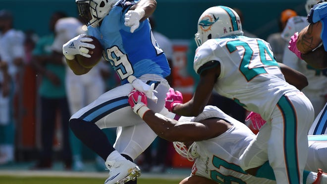 Dolphins defensive end Cameron Wake (91) reaches for Titans running back DeMarco Murray (29) during the first half Sunday.