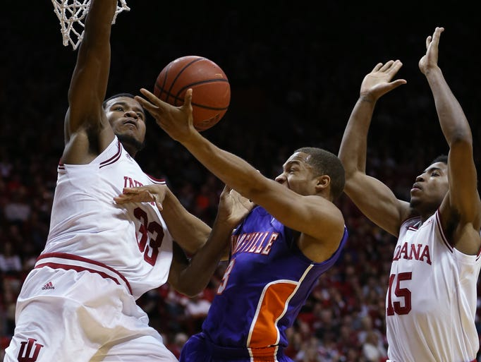 Hoosiers Jeremy Hollowell, left, and Devin Davis go up to stop Evansville guard Jaylon Brown in the first half. The Indiana Hoosiers hosted the Evansville Purple Aces at Assembly Hall on Tuesday, November 26, 2013.