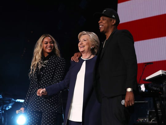 Beyonce, left, Hillary Clinton and JAY-Z appear on