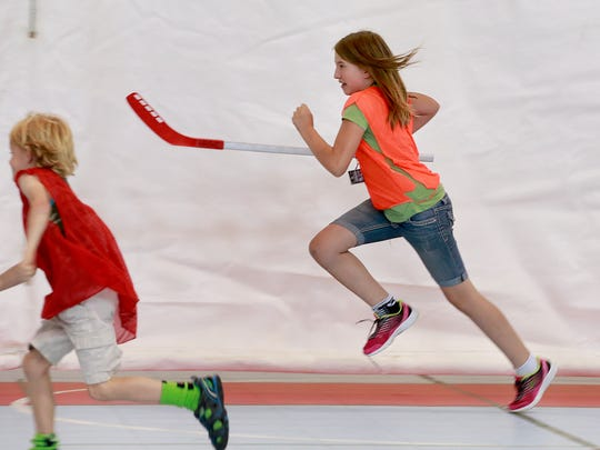 Morgan Dannar, 11, runs during a floor hockey game on Friday at the Aztec Boys and Girls Club. The nonprofit has created a new scholarship program for its summer camp, which has seen a 20 percent increase in enrollment.