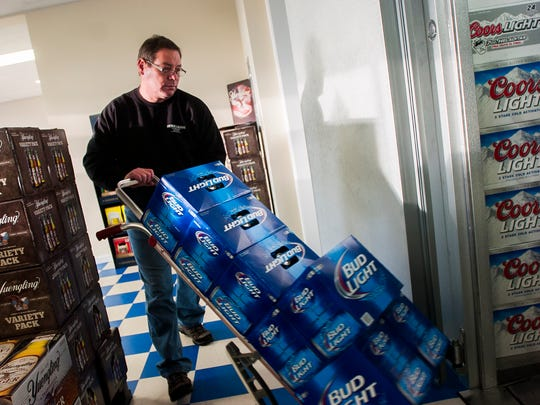 Case Beer & Beverage owner Dan Gladhill stocks cases of beer in the freezer at the beer distributor in Hanover in 2013.