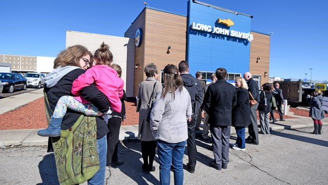 Local dignitaries wait for the ceremonial ribbon-cutting marking the remodeling efforts at the Long John Silver's on Park Avenue West.