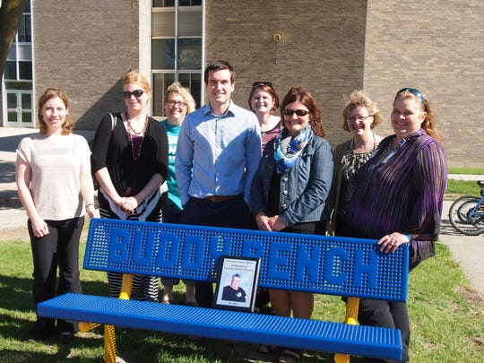 Members of Kickstarters team with Buddy Bench at Riverside Elementary School (dedicated to long time school volunteer and supporter, Grandma Sharon Minnick), front row from left are: Carrie Lauersdorf, Kondex Corporation; Amber Kilawee, Fond du Lac Area United Way; Luke Wacek, Johnsonville Sausage; Kim Spartz, Moraine Park Technical College; and project supporter, Julie Budde. Second row: family members of Grandma Minnick, along with project supporter, Kelly Peterson. Not pictured, team member Karen Befus, Action Reporter Media; and project supporters Brenda Mand, North Fond du Lac Parent Teacher Organization and the MPTC Satellite Kiwanis Club.
