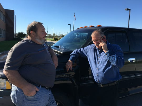 Don Zering (left), a 43-year Rexnord employee, stands outside the company's Indianapolis plant after learning Rexnord is tentatively planning to relocate operations to Mexico. Kelly Hugunin, the local representative for United Steelworkers Local 1999, takes a phone call regarding Rexnord.