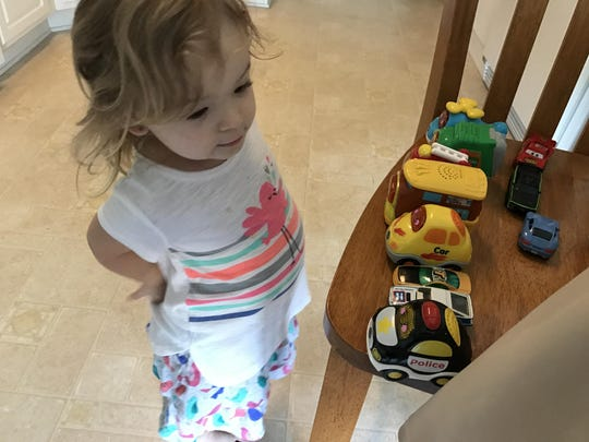 Isabella lines up her cars and recites their colors.