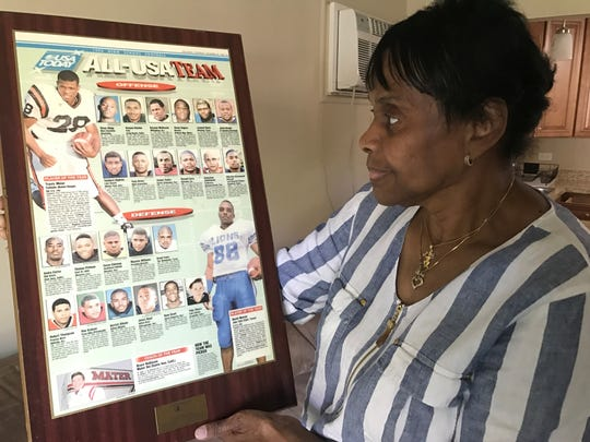 "Maggi Ross, Hubert ""Boo Boo"" Thompson's mother, looks at a framed 1996 USA Today sports page inside her apartment in Wheaton, Illinois. Thompson was named to the All-USA Team after a dominant career at Proviso West High School in suburban Chicago."