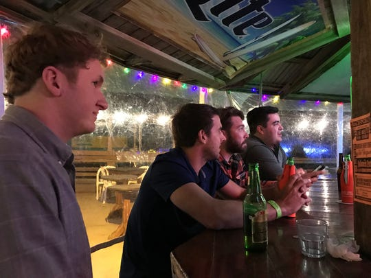 Mac Claus, 23, from left, Zach Standerfer, 25, Christian Heckel, 25, and Andrew Guido, 23, watch the Houston Astros and the Los Angeles Dodgers play in Game 3 of the MLB World Series on Friday, Oct. 27, 2017, at The Back Porch Bar in Port Aransas.