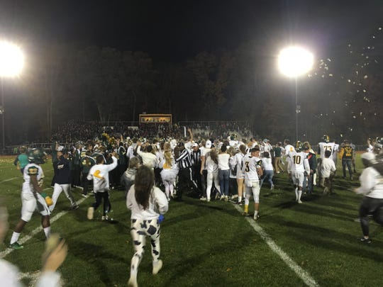 The North Hunterdons tudent section storm the field after the Lions topped Voorhees 31-23 to take the 2017 Milk Can Game