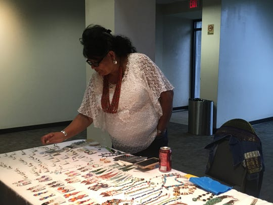 Paula Begay arranges pieces of jewelry created by her husband Abraham. The two have been selling jewelry at the Native American Art show at Angel Mounds for about six years.