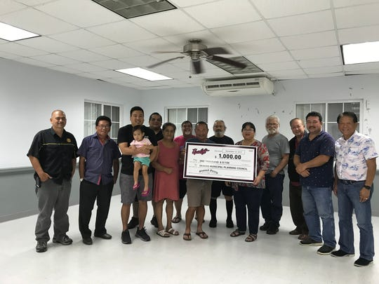 "On Dec. 12 Upshift Ent. presented a $1,000 check to the Dededo Municipal Planning Council during their monthly meeting at the Macheche Community Center. The donation was made as a contribution to the village and as a ""Thank You"" for allowing the use of the former Dededo Flea Market property to host the 2017 Slammed Society Auto Showcase in Nov. that displayed a hundred of the islands customized automobiles and attracted thousands of attendees. Pictured from Left: Jim Cruz (Upshift), Romy Acda (Council Member), Tom Akigami (Upshift Managing Director), Amelia Akigami (Upshift President), John Borja (Upshift), Carmen Tainatongo (Council Member), Pascual Artero (Council Member), Vice Mayor Frank Benavente, Felix Santos (Council Member), Mayor Melissa Savares, Ernie Wusstig (Council Member), Bernie Gines (Council Member), Glenn Makepeace (Council Member), Art Chan (Council Member)."