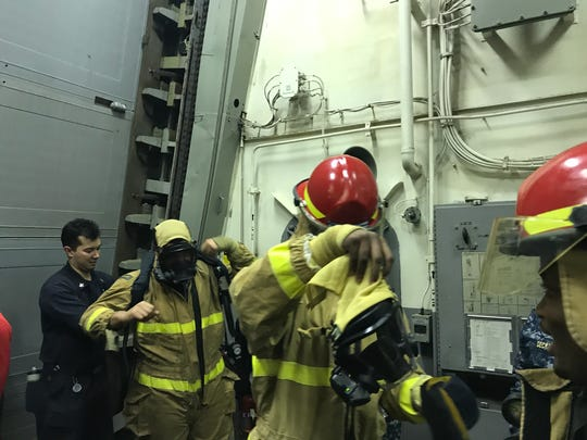 Louisville wide receiver Devante Peete tries on a fire suit and helmet on the USS Farragut at the Naval Station Mayport on Thursday.