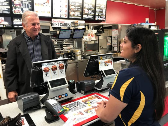 Carl Karcher, president of Carl's Jr., takes an order from an Indio High School student.