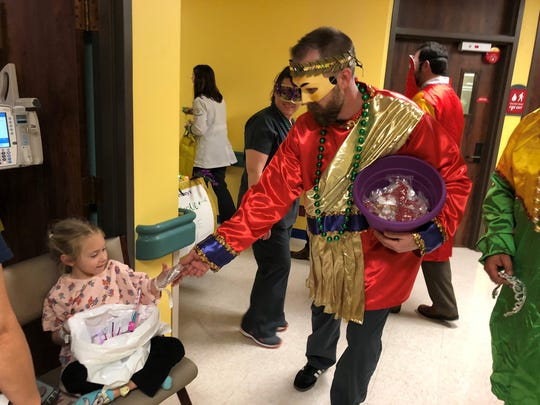 A Mardi Gras with the Krewe of Gabriel hands beads to Rylee Romero, 4, at Women's & Children's Hospital during the sixth annual Mardi Gras parade Friday, Feb. 9. 2018.
