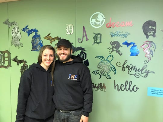 Tough Weld Fabrication owners Amanda and Charlie Penrod stand in front of a wall of their plasma-cut metal art.