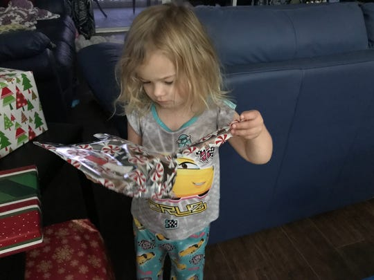 Isabella opens a present this past Christmas.