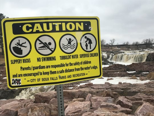 A sign in Falls Park warning of the dangers present