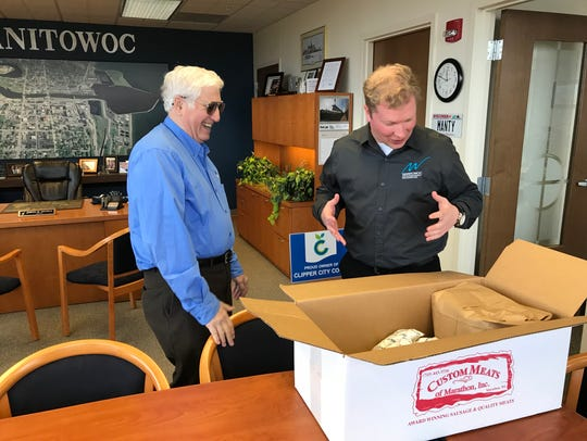 Manitowoc Mayor Justin Nickels (right) opens a box
