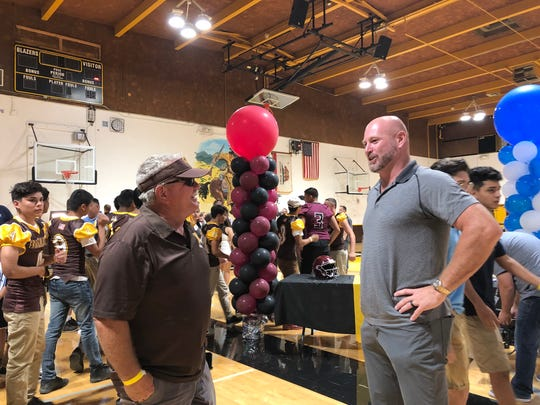 Golden West offensive coordinator Stan Kanawyer speaks with Super Bowl champion and former Fresno State QB Trent Dilfer on Tuesday at Golden West High School.