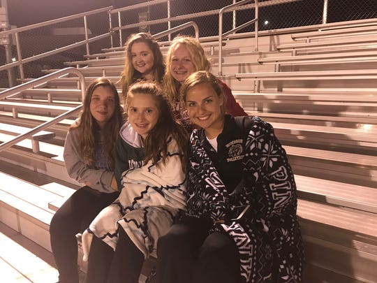Clockwise from back left: Maralee Bixby, 17, Haley Mckee, 18 Morgan Bryant, 15, Alexis Hendrickson, 17, and Lizzie Strong, 17, observe Windsor football's midnight practice Monday.