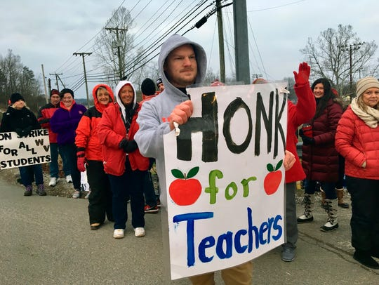 Striking teachers wave at passing cars outside Poca
