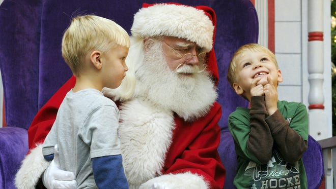 Josiah Eastman looks on as his brother Hunter thinks about what he wants to ask Santa Claus at the York Galleria Mall on Thursday, Dec. 5, 2013.