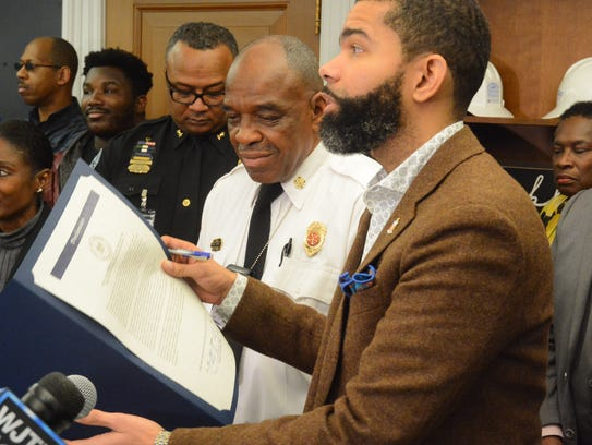 Mayor Chokwe Antar Lumumba gets ready to sign an executive order Monday that bans the release of mug shots of persons involved in officer-involved shootings.