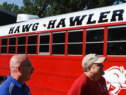 Wes Henderson (left) and Rob Coleman check out the Hawg Hawler, a bus they purchased and converted into the ultimate football road trip ride. They travel to nearly every Razorback game with family and friends.