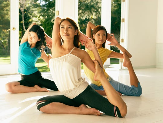 Three young women in pigeon pose