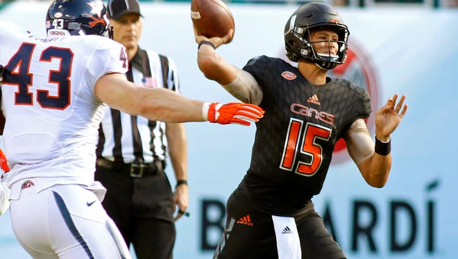 Miami quarterback Brad Kaaya (15) throws under pressure from Virginia defensive end Trent Corney (43) in the first half of an NCAA college football game, Saturday, Nov. 7, 2015, in Miami Gardens, Fla. Miami won the game 27-21. (AP Photo/Joe Skipper)