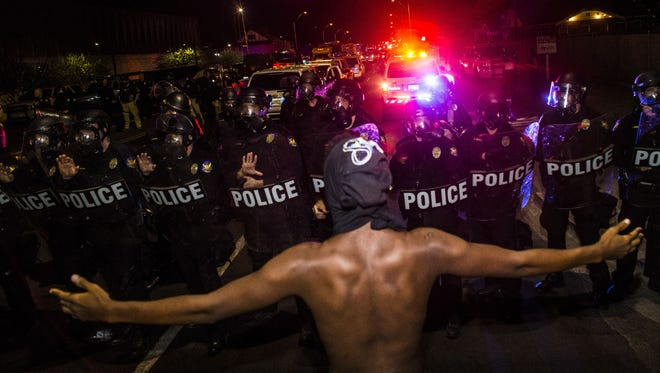 A Black Lives Matter activist throws out his arms as police stop the Black Lives Matter marchers from continuing on Seventh Street on July 8, 2016, in Phoenix. The protester in the iconic photo was later identified as 17-year-old Devin Draper of Buckeye.