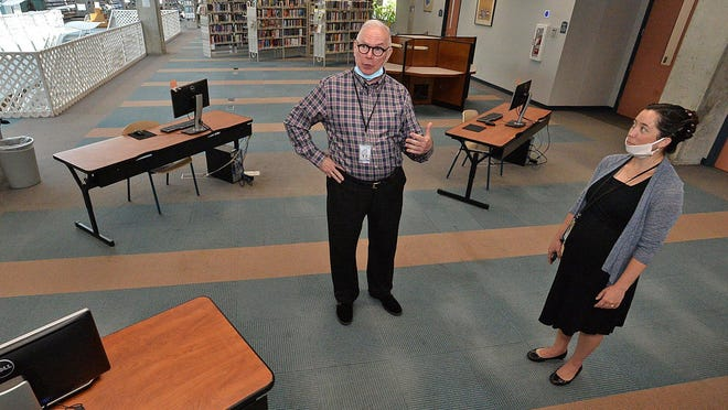 Library Director Blane Dessy, at center, and Assistant Director Sheryl Thomas, at right explain how the computers have been spread out for better social distancing in the internet lab at Blasco Memorial Library in Erie. The Erie County Public Library system reopened for in-person service on Monday, but Sunday service will not available through the end of 2020.