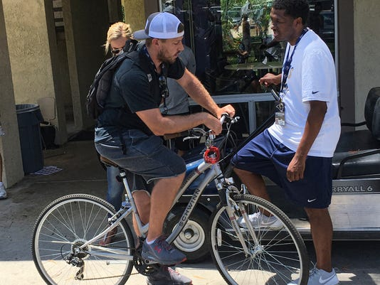 Rams quarterback Case Keenum leans on his bicycle as he speaks with team spokesman Artis Twyman, right, after the Rams' veterans reported to training camp in Irvine, Calif. on Thursday, July 28, 2016. The Los Angeles Rams' veterans gathered in Orange County for the start of a five-week residency at UC Irvine while their permanent in-season home is built in Thousand Oaks. They'll have plenty of time together to prepare for their homecoming season in California. (AP Photo/Greg Beacham)