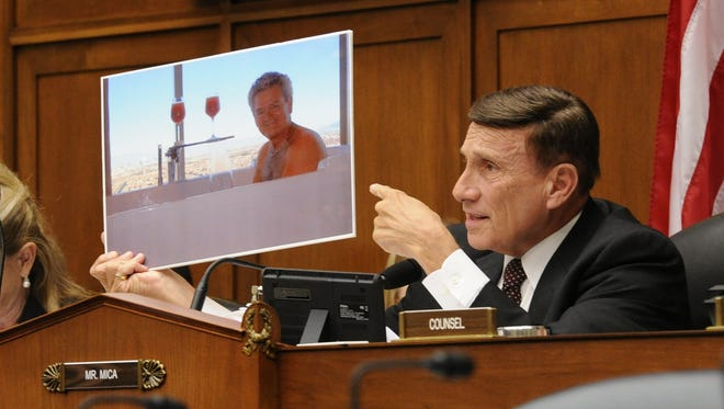 Rep. John Mica, R-Fla., holds up a photograph of a GSA employee in a Las Vegas hot tub at a House committee hearing on wasteful travel spending.