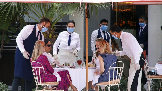 A group of women are served their lunch Monday on the outdoor patio at St. Ambroeus in Palm Beach.