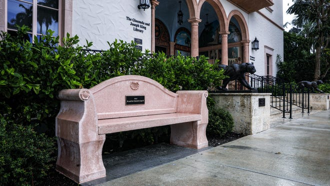 """One of two cast concrete pink benches, this one labeled """"Gift of Mr. and Mrs. Frederick M. Alger III,"""" sits in front of The Society of the Four Arts King Library, June 18, 2020."""