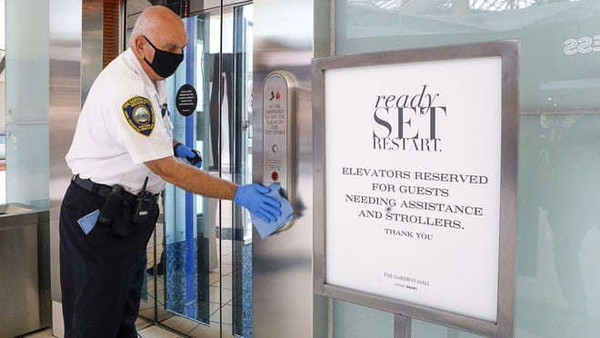 A security guard wipes down the elevator area on the second floor of The Gardens Mall, which reopened Friday morning after closing in March amid coronavirus concerns.The mall will require all of its employees to play a role in keeping the mall clean.