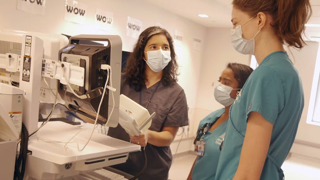 In this August photo provided by the Mount Sinai Health System, neurologist Dr. Alexandra Reynolds holds part of a device that tracks blood flow in the brain, at a hospital in New York.