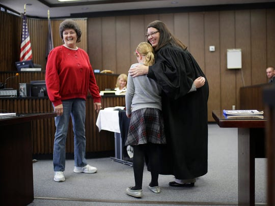 Judge Angela Sutkiewicz hugs Vayda Sonnenberg, 8, of