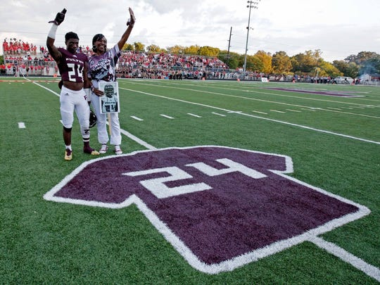Zenobia Dobson, right, and Zack Dobson wave to the crowd as a jersey of Fulton football player Zaevion Dobson is unveiled before their game against Maryville in August 2016. Zaevion Dobson was killed shielding friends during a drive-by shooting.